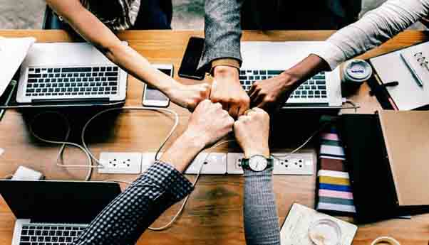 Several hands joined together while working in startup